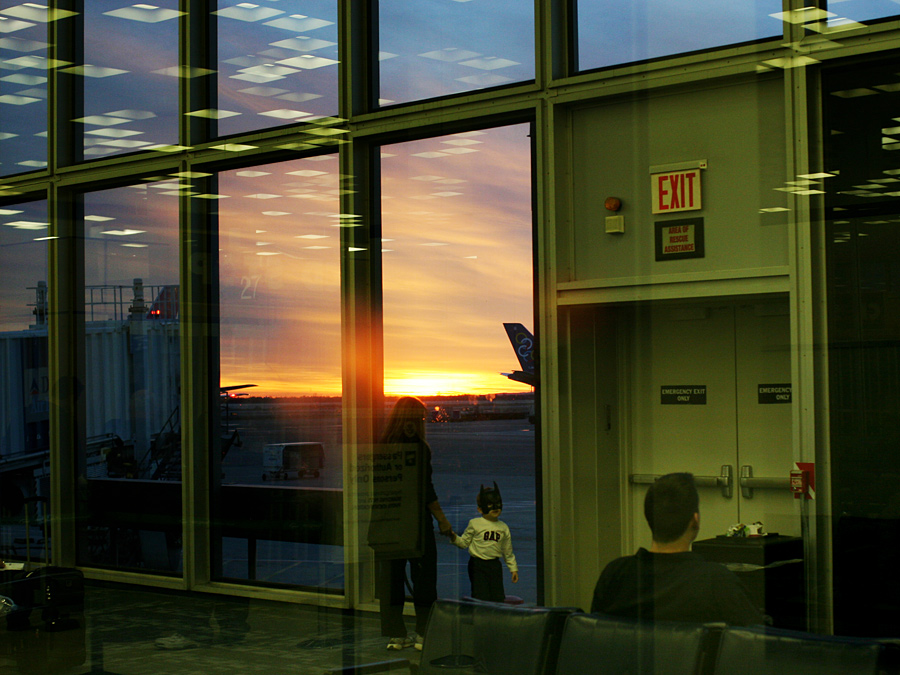 A Boy in a Mask Turns Aways from a Sunset at JFK